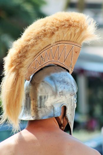 Rear view of shirtless man wearing knight helmet during event