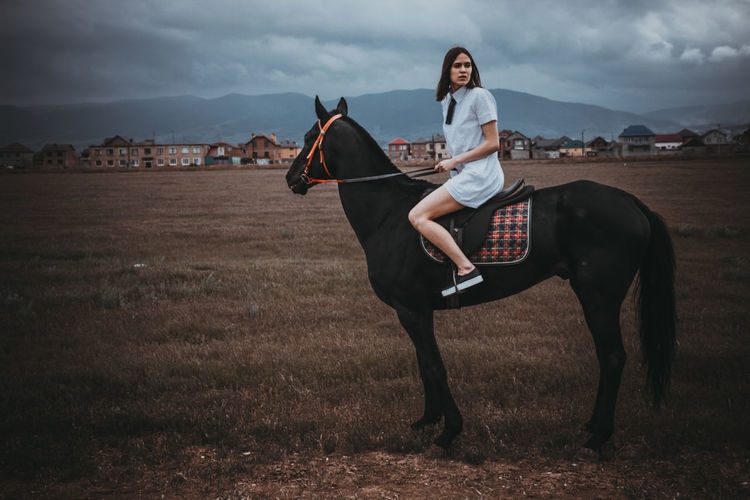 Woman and horse on field against cloudy sky