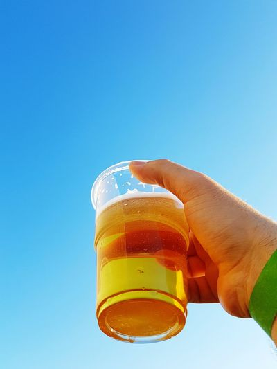 Cropped hand holding beer against clear blue sky