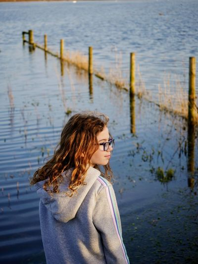 Girl looking away while standing by lake