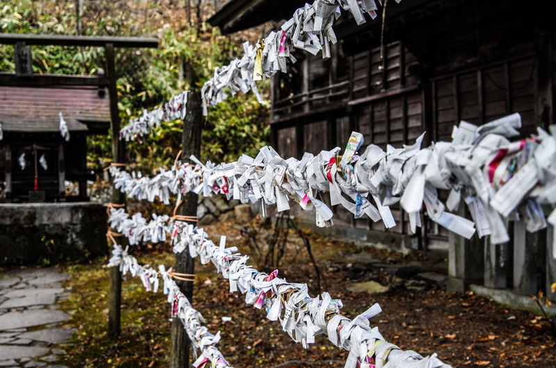 Papers hanging on railing at temple