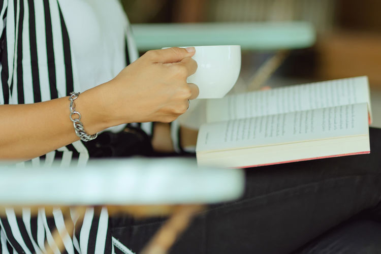 Close up of female reading book and drinking coffee in coffee shop. Relaxed Moments Book Coffee Cup Reading & Relaxing Reading Reading A Book Read Reading Reading Glasses E-reader Sending Coffee Knowledge Hardcover Book Literature Black Coffee Workbench Text Messaging