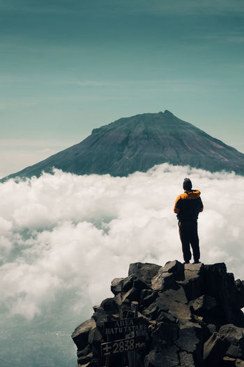 A man standing on rock at approximately 2800m above sea level facing to a mountain or strato volcano