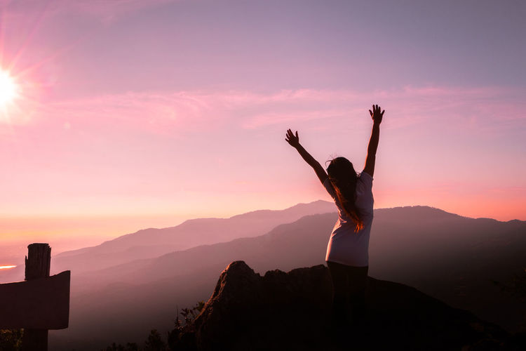Rear View Of Woman With Arms Raised Standing On Mountain During Sunset