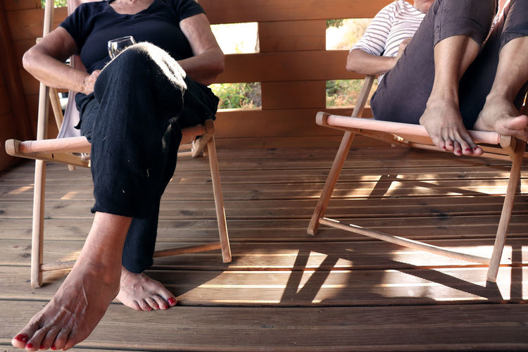 Low section of people sitting on wood