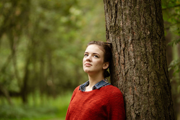 Portrait of evelina  against tree trunk in forest