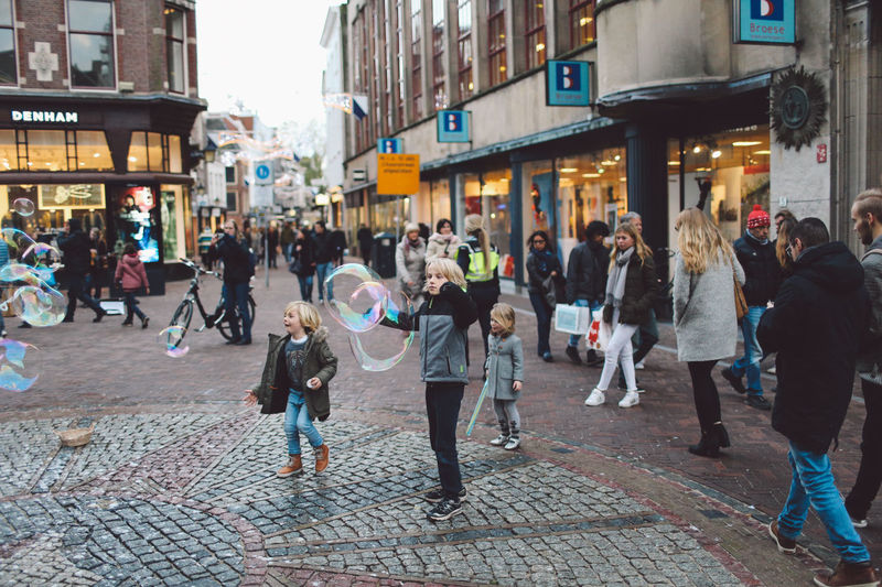Architecture Bubbles Building Exterior Built Structure Children City City Life Crowd Day Illuminated Large Group Of People Men Outdoors People Playing Real People Soap Bubbles Women Enjoy The New Normal