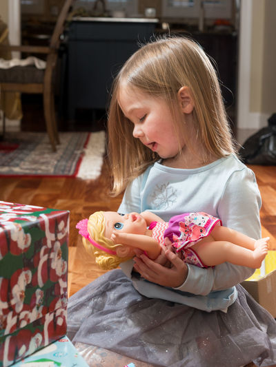 Girl Playing With Doll At Home