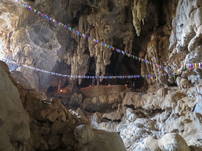 Beauty In Nature Bunting Cave Celebration Hanging High Angle View Holy Laos Outdoors Religion Religious  Rock - Object