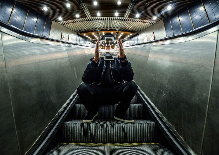 Headless man sitting on escalator
