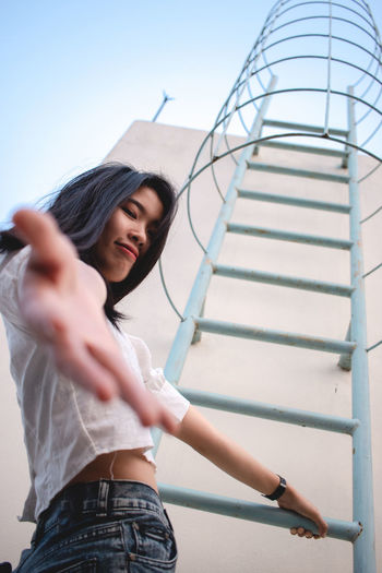 Low angle portrait of woman climbing on ladder