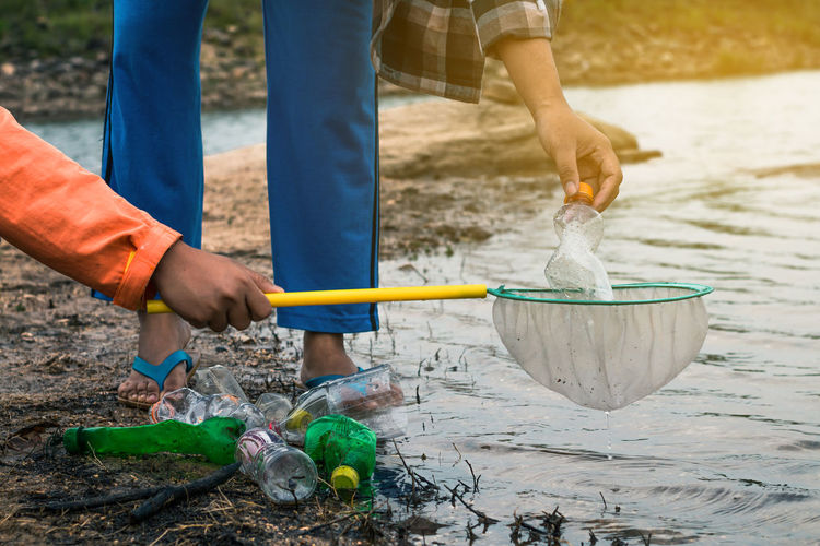 Low section of volunteers removing plastic bottles from lake