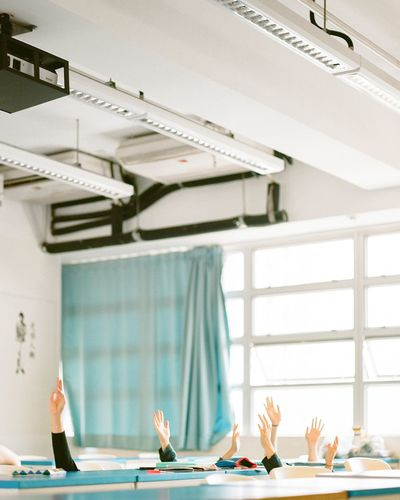 Cropped Image Of Hands Raised In Classroom