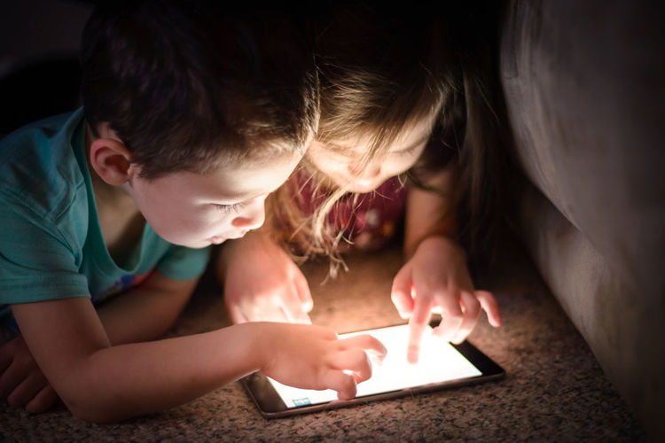 Close-Up Of Siblings Using Digital Tablet While Lying On Floor In Darkroom