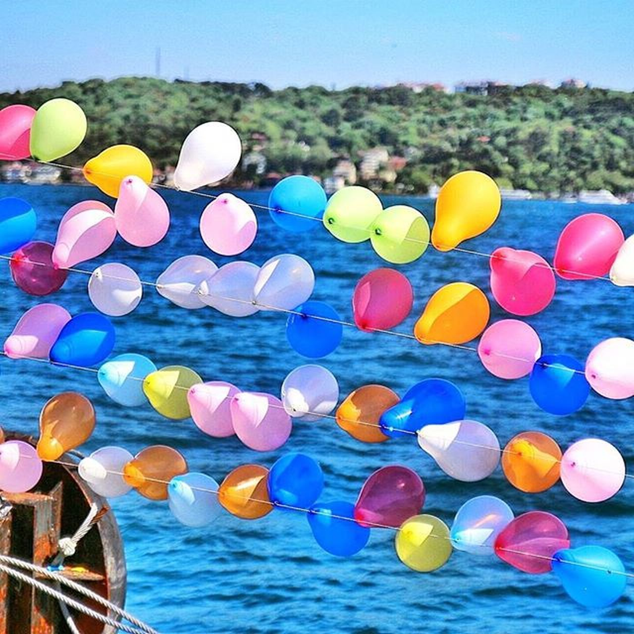 multi colored, outdoors, balloon, large group of objects, sea, day, blue, water, no people, celebration, nature, sky, close-up