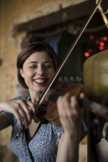 Smiling woman playing violin