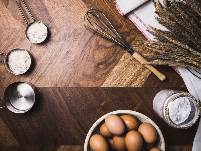 Directly above of eggs and wire whisk on table