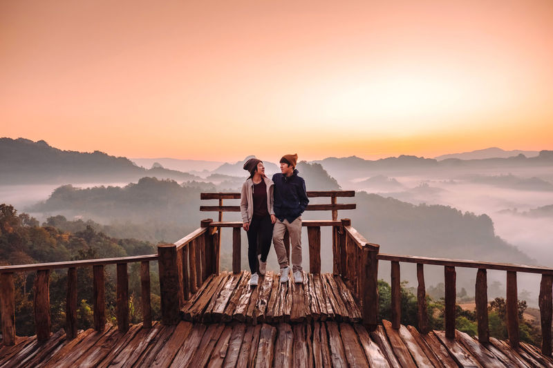 Rear view of men standing on mountain against sky during sunset