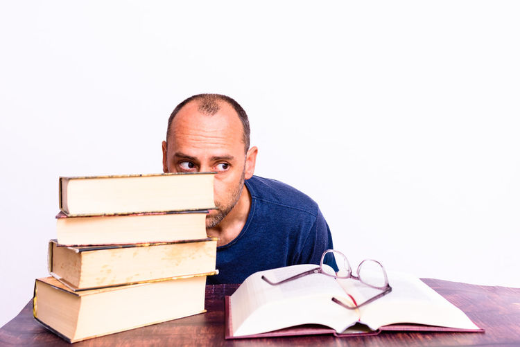 Portrait of a man with books on table