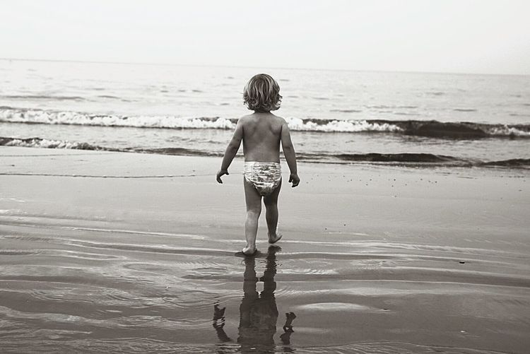 Rear view full length of girl on shore at beach