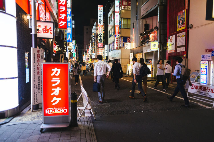 Neon signs and salary men in Shinjuku Architecture Built Structure City City Life City Street Communication Day Directional Sign Information Information Sign Outdoors Red Road Sign Sign Text Western Script
