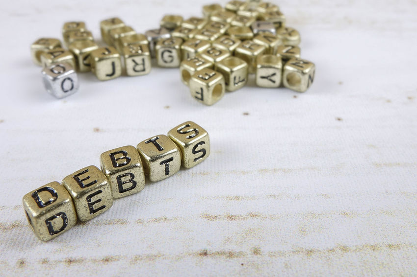 DEBT CONCEPT WITH GOLD DICE ON A WOODEN TABLE Arts Culture And Entertainment Capital Letter Close-up Communication Credit Card Debt Crisis Education Focus On Foreground High Angle View Indoors  Large Group Of Objects Leisure Games Letter No People Number Still Life Studio Shot Table Text Toy Western Script Wood - Material