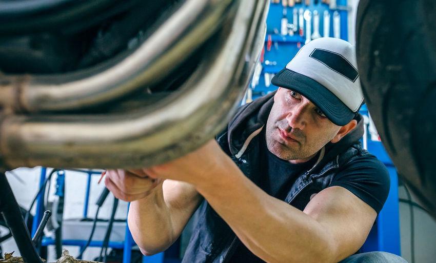 Mature mechanic repairing motorcycle in garage