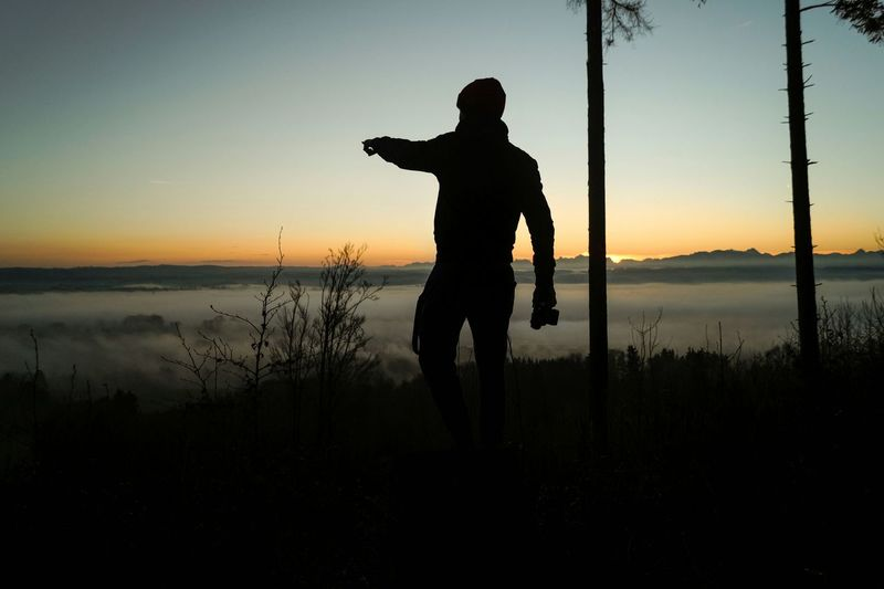 Silhouette man pointing in forest against sky during sunset