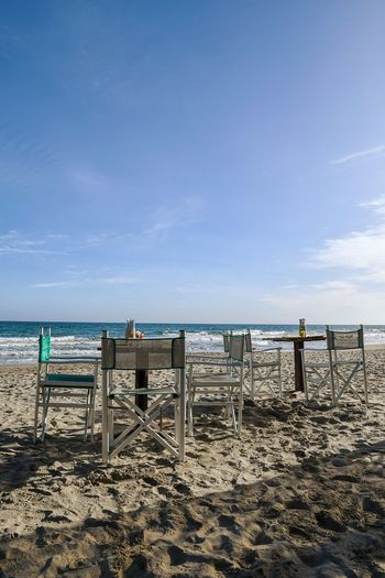 tables and chairs on the beach Beach Bar Tables And Chairs On The Beach On The Sand Beach Sea Blue Empty Beach Tranquility No People Silence Travel Destinations Travel Seascape Wintertime Sea In Winter Winter Beach Modern Hospitality