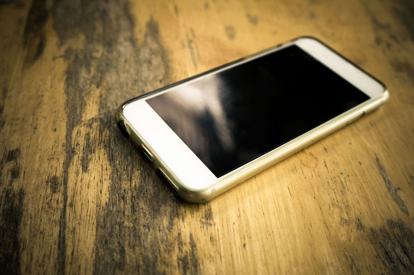 Smart phone in white color with blank screen laying on wooden table 4g 5G Cellphone Mobile Phone Smart Phones  Wood Cellular Communication Connection IPhone Internet Laying Mobile Network Phone Smart Phone Technology White Background Wifi Wireless Technology Wirless Wood Table Wood Table Background Wood Table Top Wood Tables