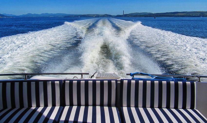 Sea waves splashing on boat against sky
