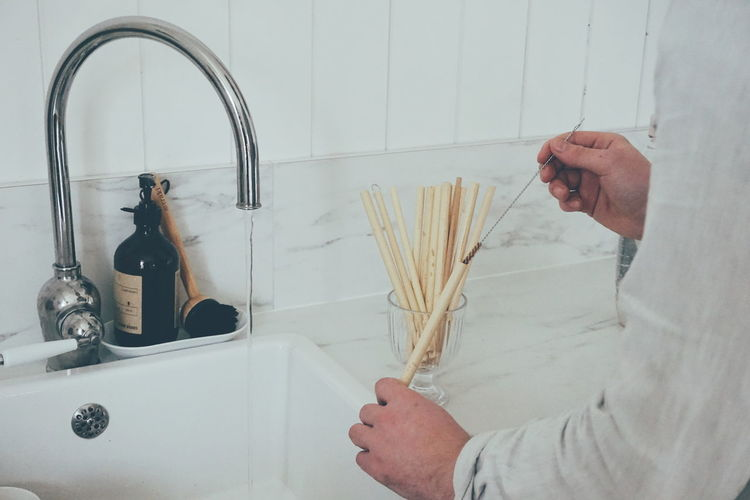 Close up of young man washing reusable bamboo straw at the kitchen sink