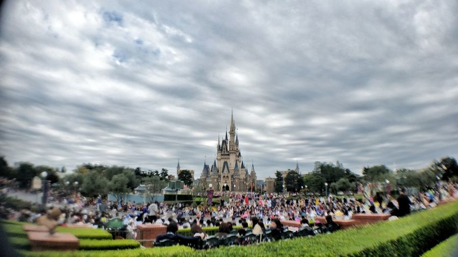People at town square against cloudy sky