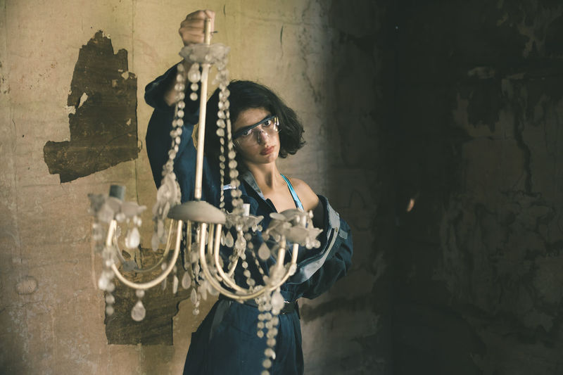 Portrait of young woman holding chandelier while standing against wall