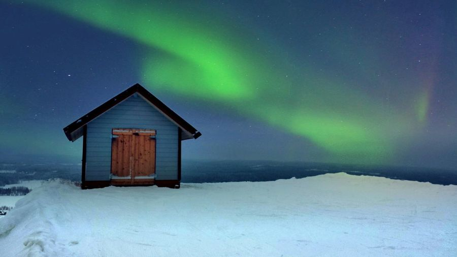 House On Snow Landscape Against Northern Lights