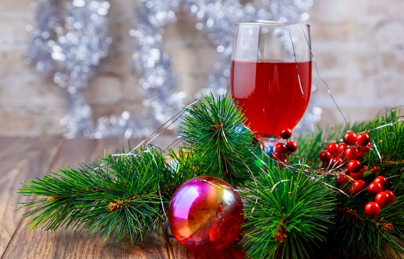 Close-Up Of Red Wine In Wineglass Amidst Christmas Decorations On Table