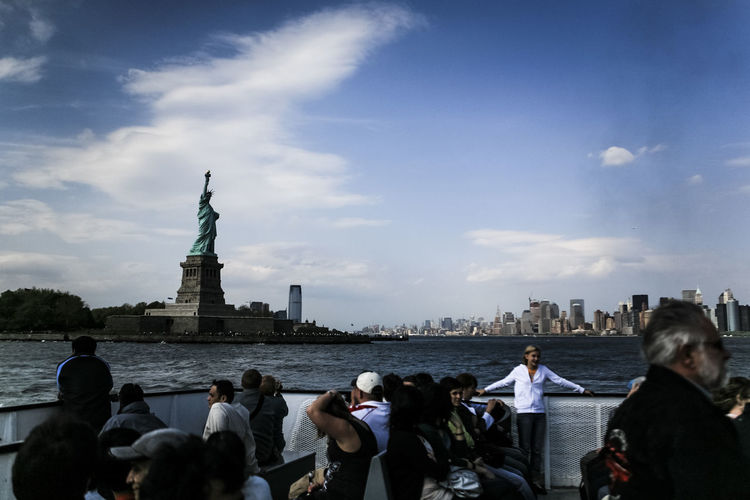 Tourists Looking At Statue Of Liberty In City Against Cloudy Sky