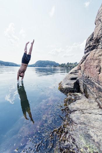 Man standing on rock in water against sky