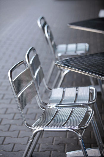 Aluminium furniture on the pavement Seat Absence Empty Chair No People Metal Focus On Foreground Table Day Arrangement Business Furniture Still Life Silver Colored Close-up Gray Outdoors In A Row Aluminum Pavement
