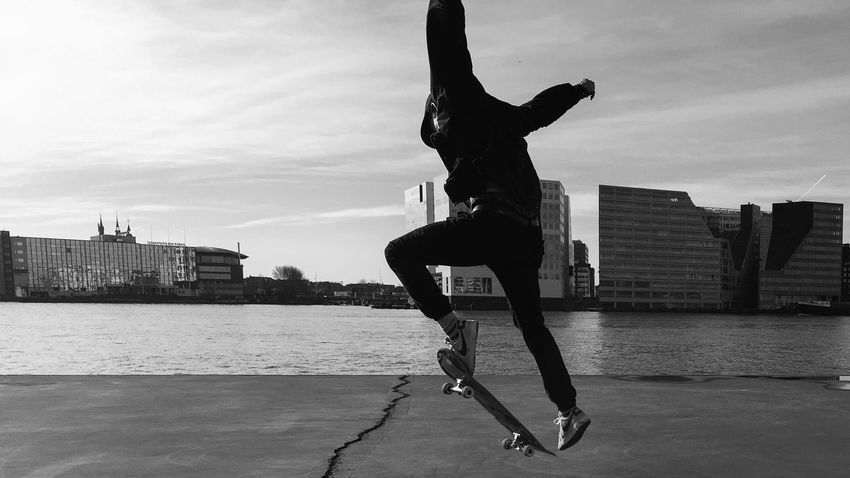 Waterfront Water Twist Sky Skateboarding Skateboard Ride Puddle Outdoors Hat Concrete City Life City Blackandwhite Amsterdam Sport Bird Fly Capture The Moment Capturing Movement
