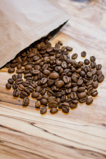 Food And Drink Coffee - Drink Table Food Coffee Freshness Brown Large Group Of Objects High Angle View Roasted Coffee Bean Indoors  No People Wood - Material Still Life Close-up Seed Abundance Focus On Foreground Selective Focus Spilling Caffeine
