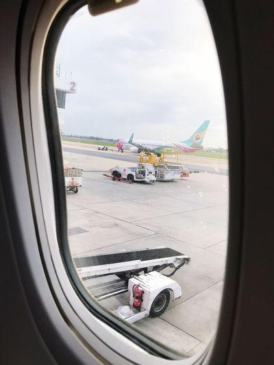 Airplane on airport runway against sky seen through window