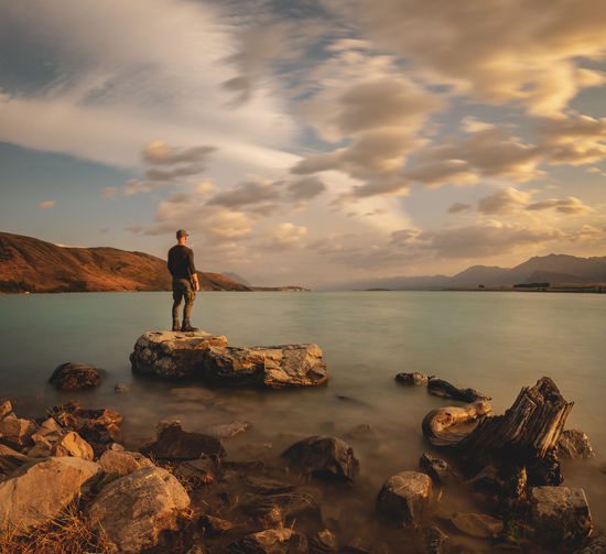 Man standing on rock by sea against sky during sunset