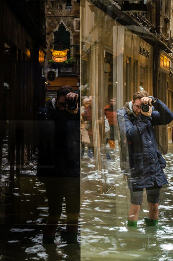 Reflection of man photographing in water on street