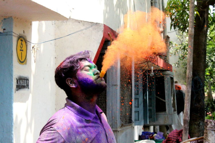 Close-up of man exhaling power paint during holi