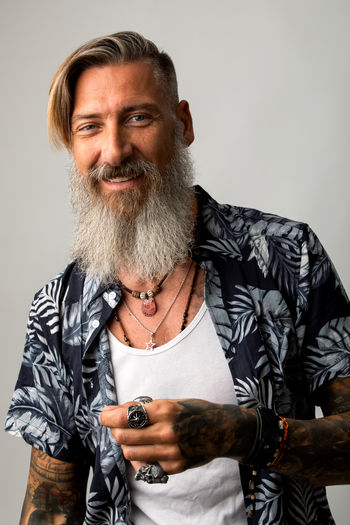 Portrait of an attractive cheerful man with a beard isolated on a white background Beard Bearded Cheerful Isolated Tattoo Casual Clothing Looking At Camera Studio Shot Jewelry Rings Hipster Biker Modern Model Posing Shirt Gray Background Friendly Jeans Smart Smiling Portrait Tattooed Men person