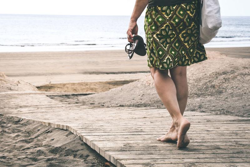 Low section of woman walking on boardwalk leading towards beach