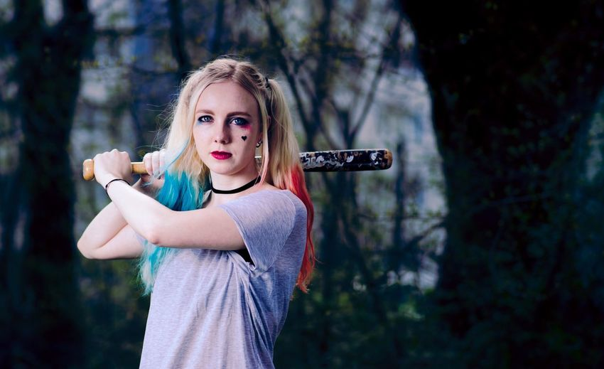A very unusual portrait. The dark colors highlight the eerie mood... Portrait Eerie Scary Aggressive Girl Weird Outfit Outfit Blue And Red Looking At Camera Deep Stare Baseball Bat Killer Dangerous Unpredictable Outdoors Forest One Person Unusual Women Blond Hair