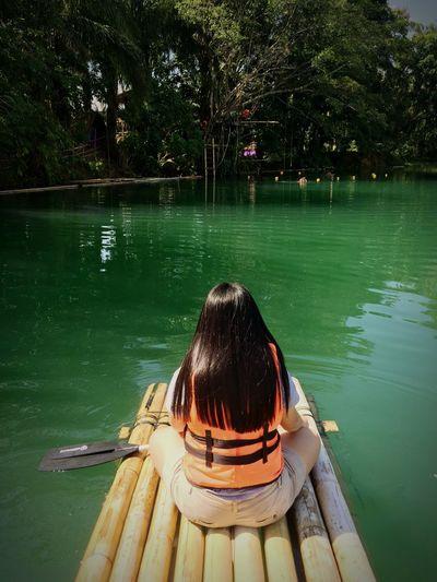 Rear view of woman sitting on pool raft in lake