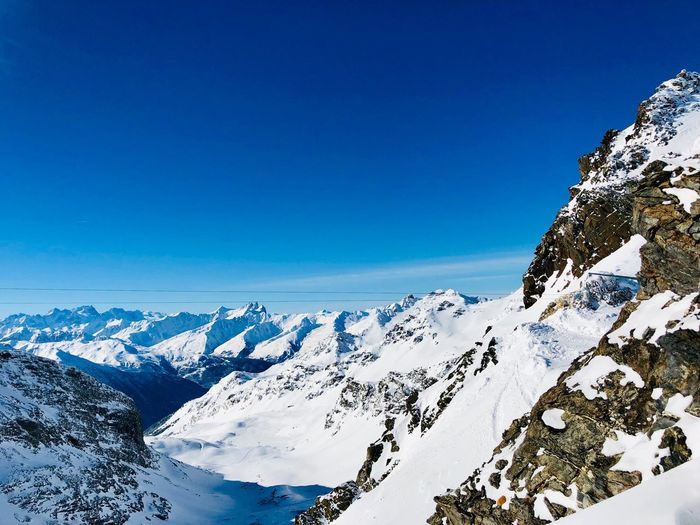 Ice Crystal Skiing Ski Area Sky Blue Beauty In Nature Clear Sky Nature Cold Temperature Winter Snow No People Tranquility Scenics - Nature Day Tranquil Scene Low Angle View Copy Space Snowcapped Mountain Mountain Outdoors Tree
